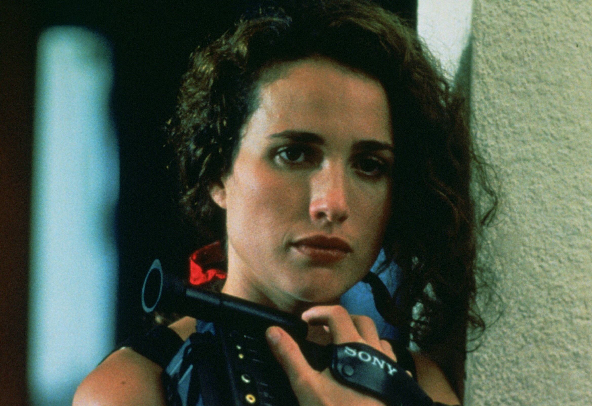 Andie MacDowell looking towards the camera, wistfully holding a camcorder