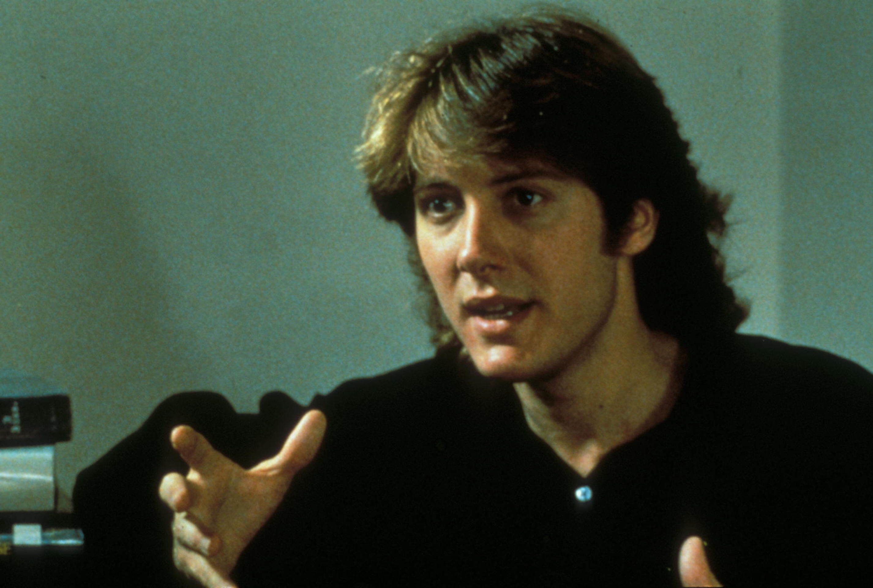 James Spader with a mullet, gesturing towards the camera