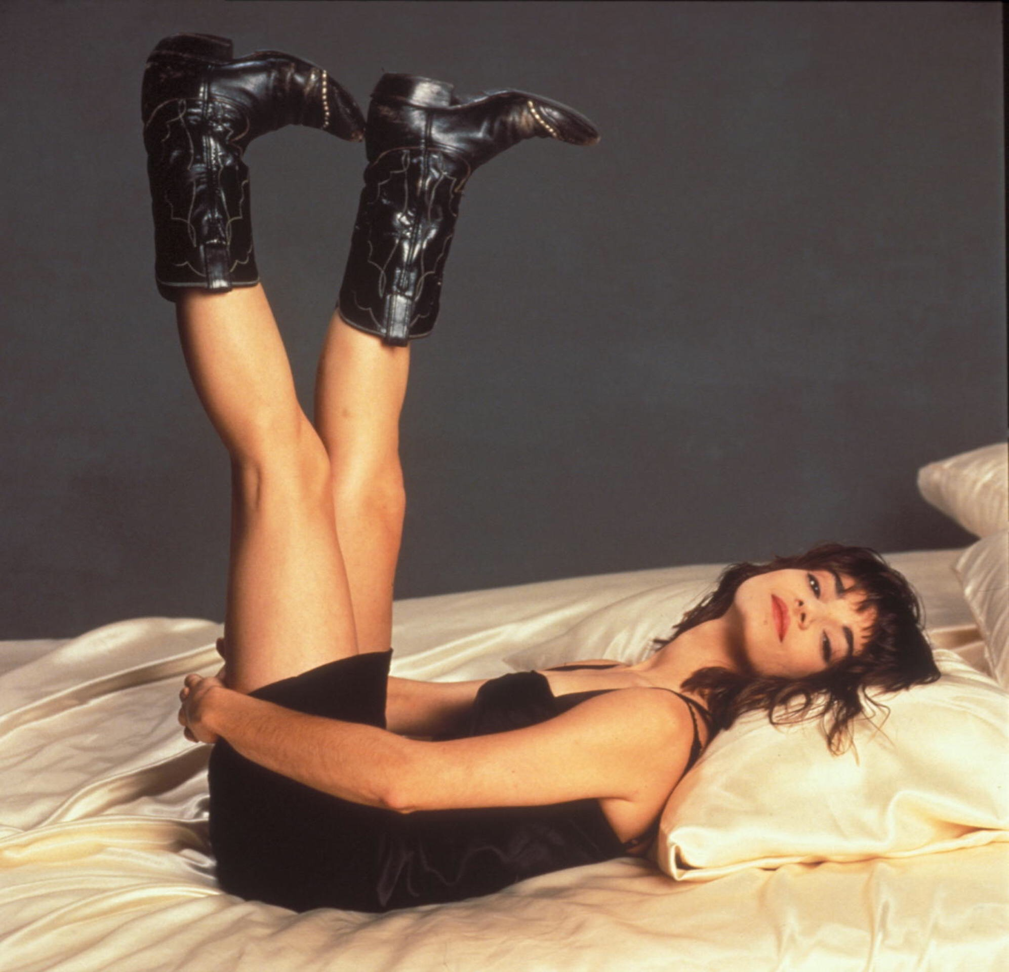 Laura San Giacomo lying on her back with her feet in the air, wearing a black dress and black boots