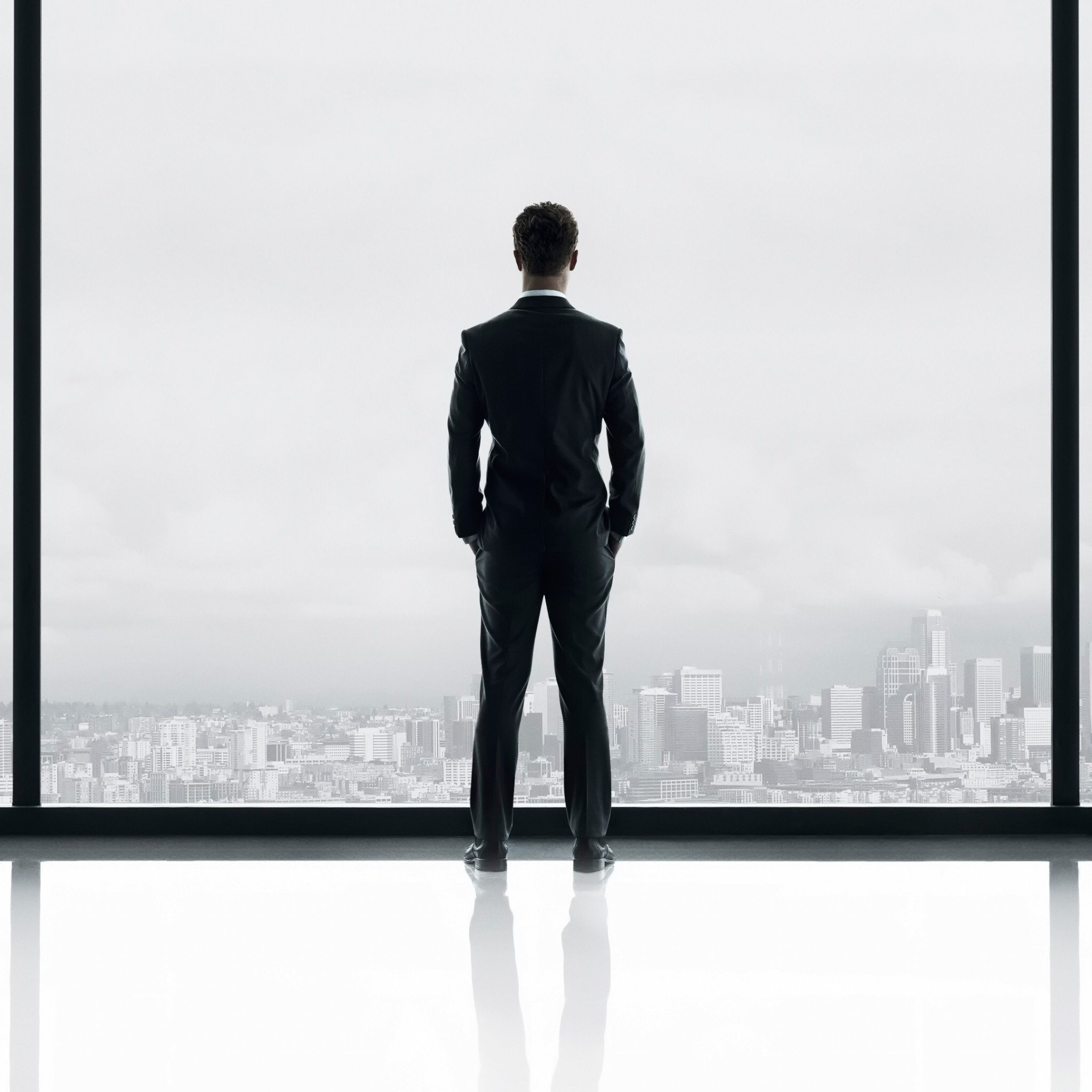 Christian Grey, standing in a window looking out over Seattle