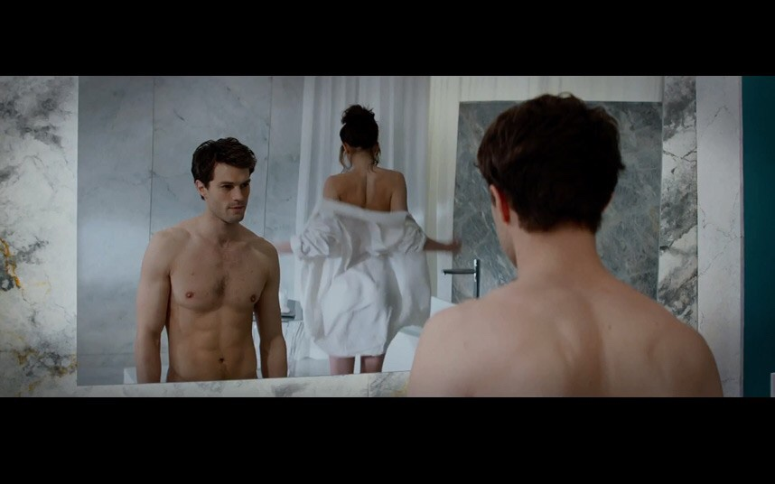 A view unto a mirror showing a top less Christian looking at Ana, who is walking away wearing his white shirt