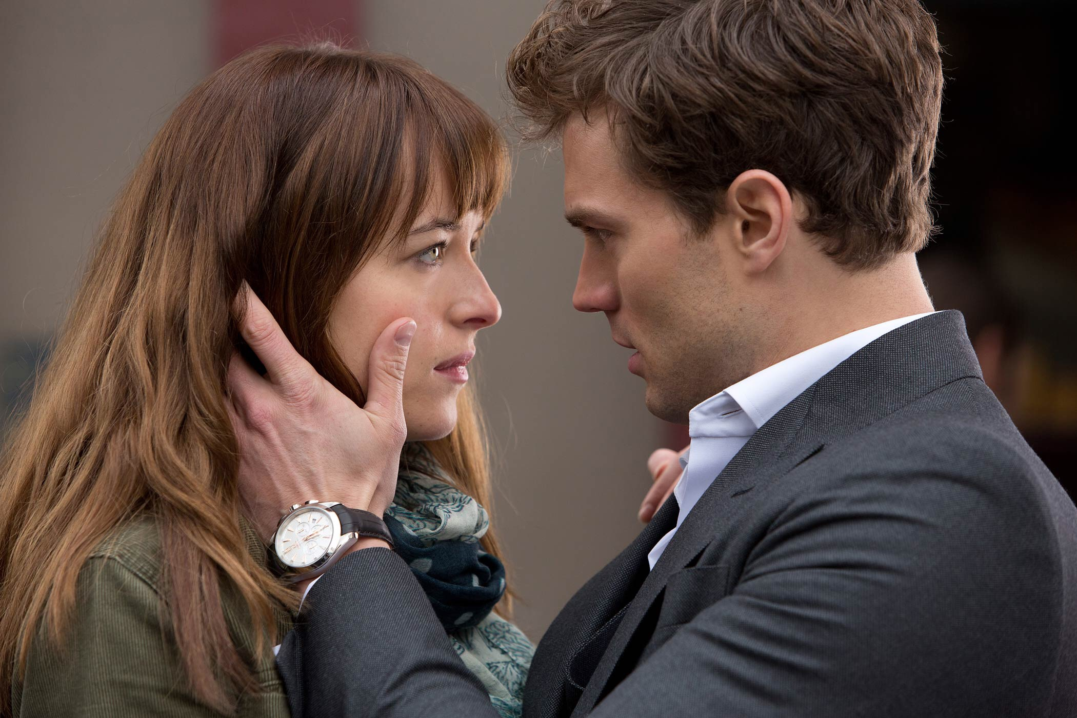 Christian is facing Ana and holding her face in his hands