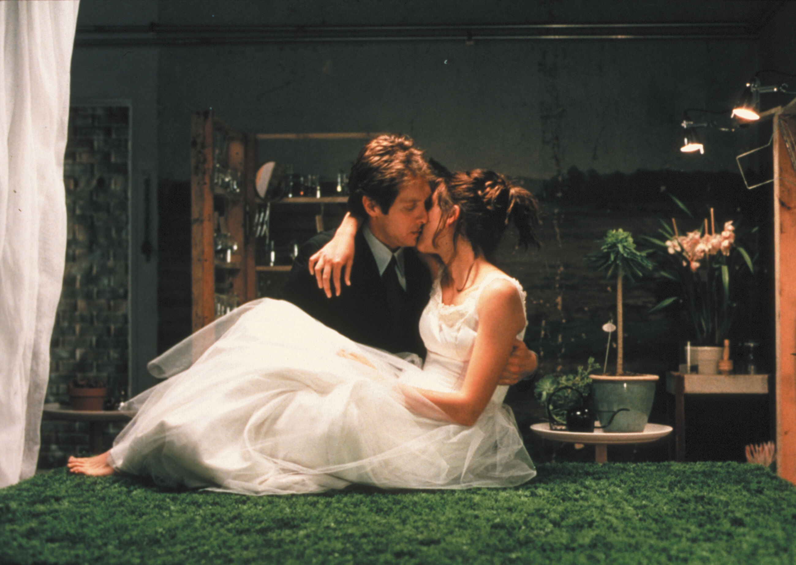 Lee is wearing a wedding dress and being held by Mr Grey as he lays her down on a box covered in astroturf