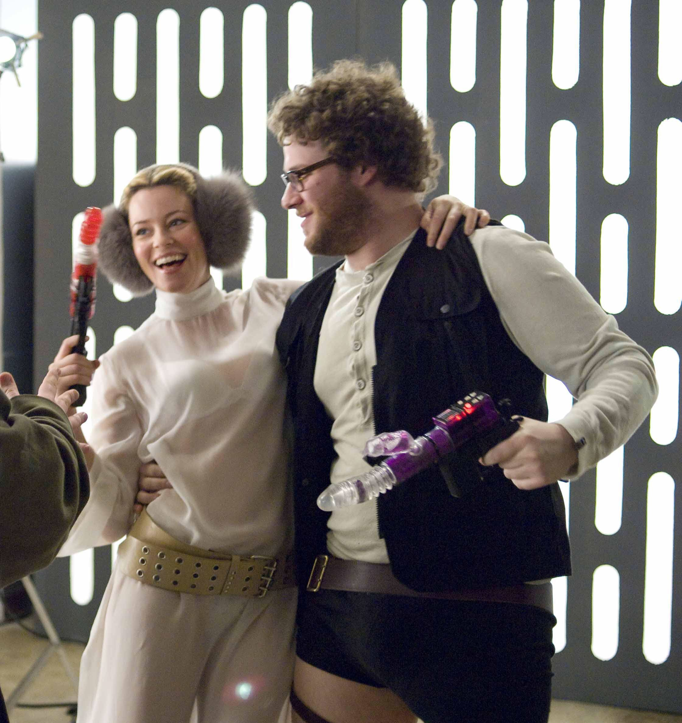 Zack and Miri are dressed as Princess Leia and Han Solo. They are embracing and holding fake weapons decorated with sex toys