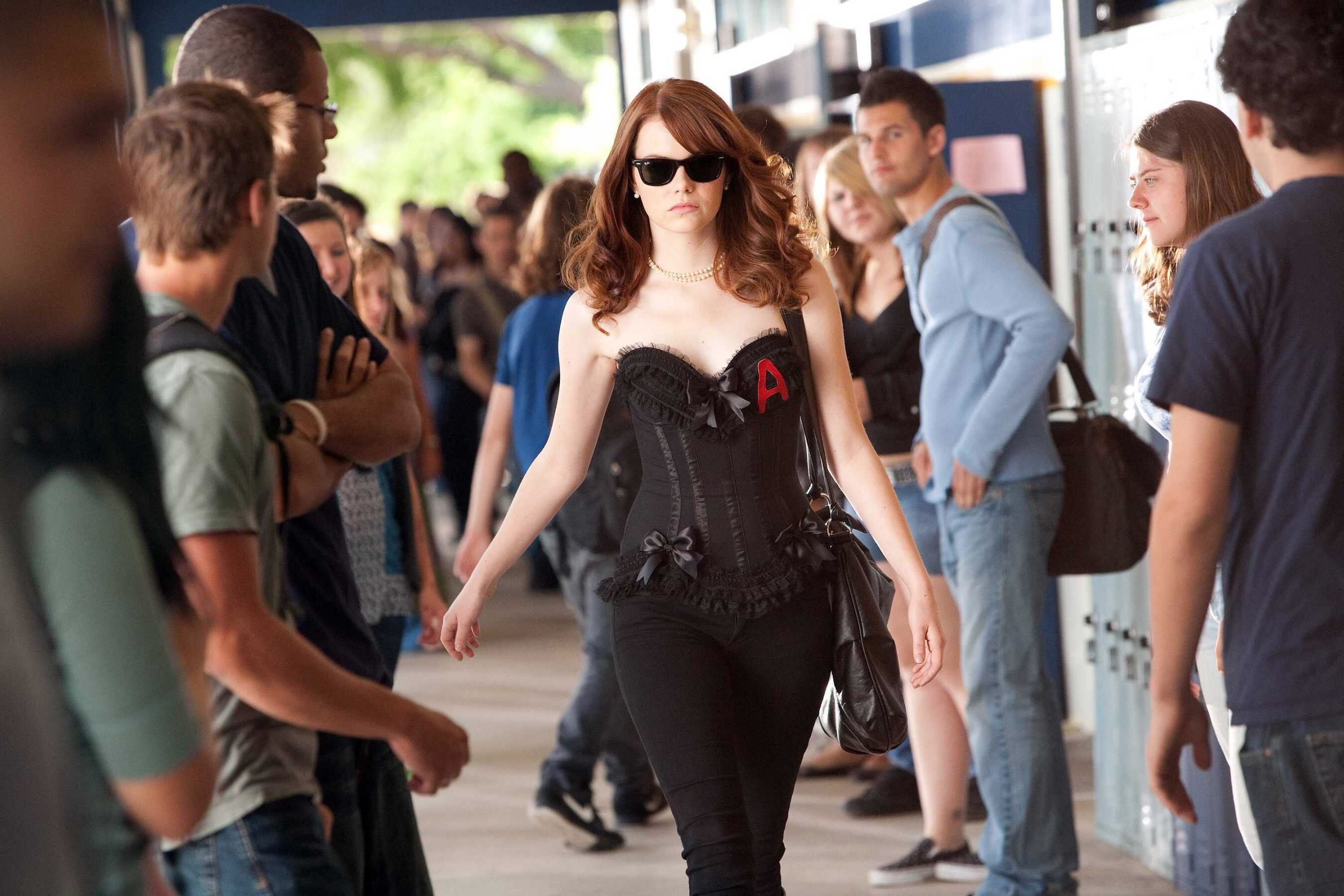 Emma Stone walking through high school wearing jeans, sunglasses and a black corset labelled with a red A