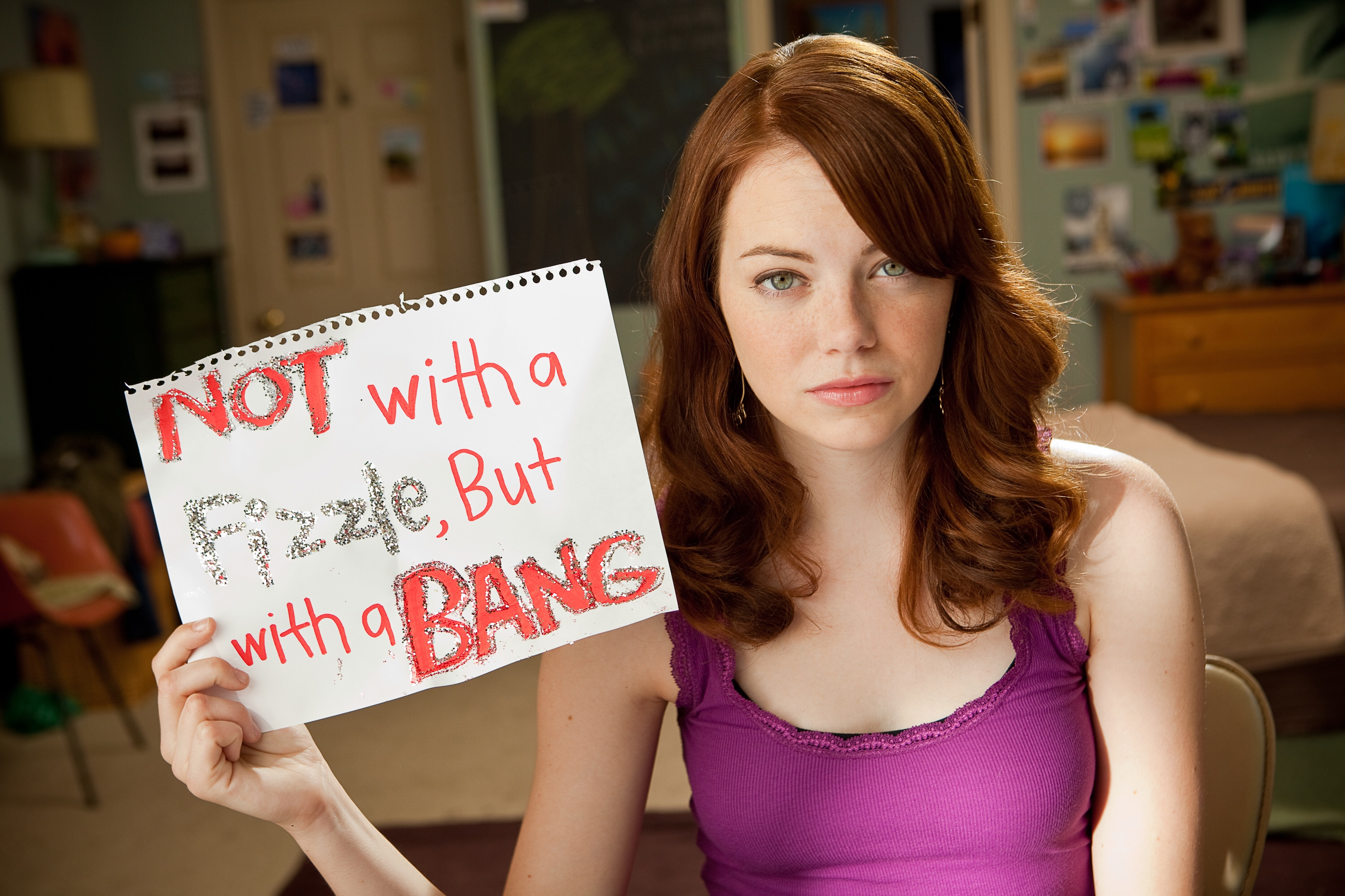 Stone facing the camera, holding a sign that says 'not with a fizzle but with a bang'