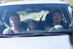 Image from the Before Trilogy of Jesse and Céline are in a car with their daughters asleep in the background