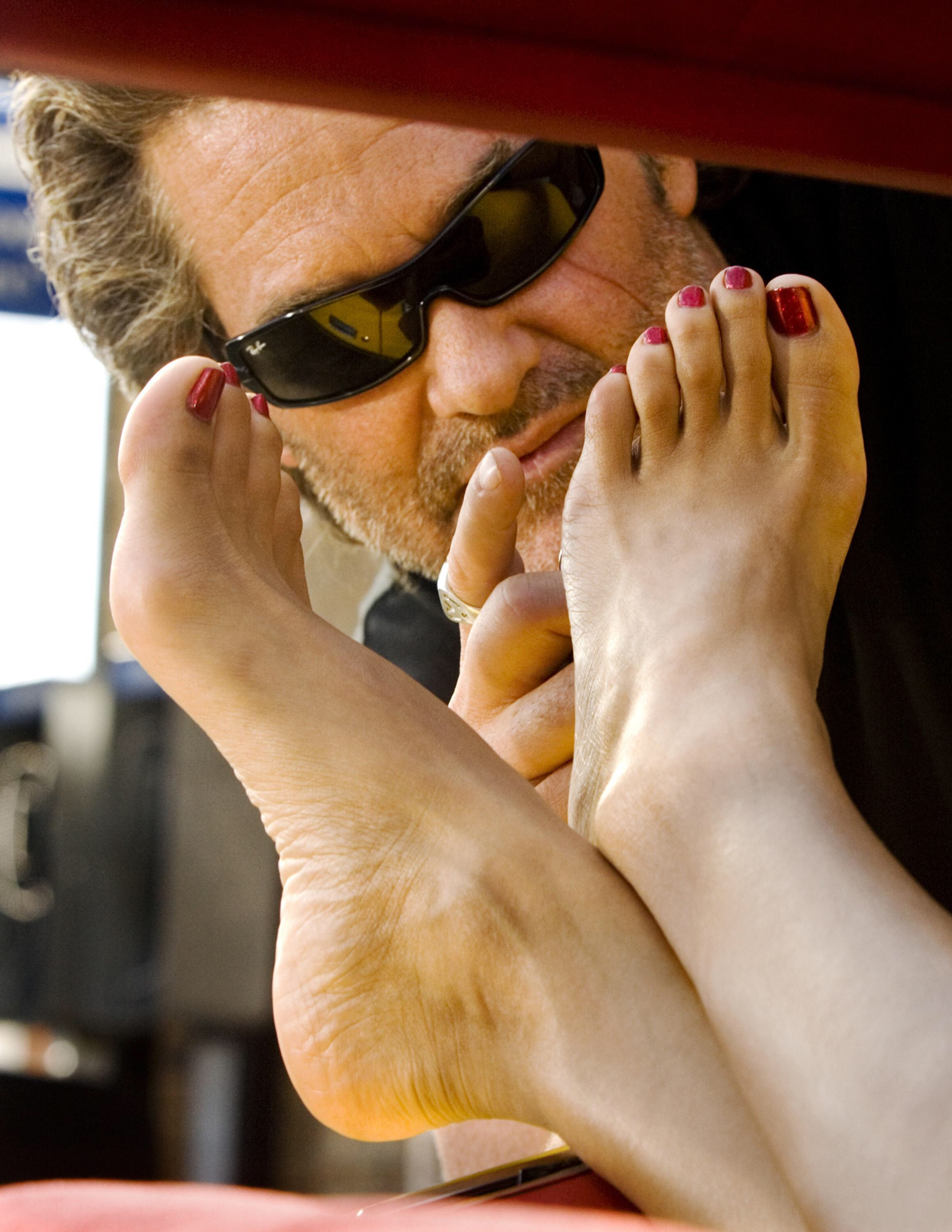 Kurt Russell about to stroke a pair of bare feet sticking out of a car window