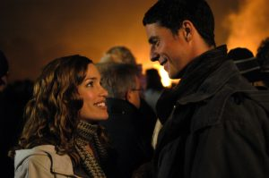 An image from Imagine Me and You of Perado and Goode smiling at each other at a bonfire party