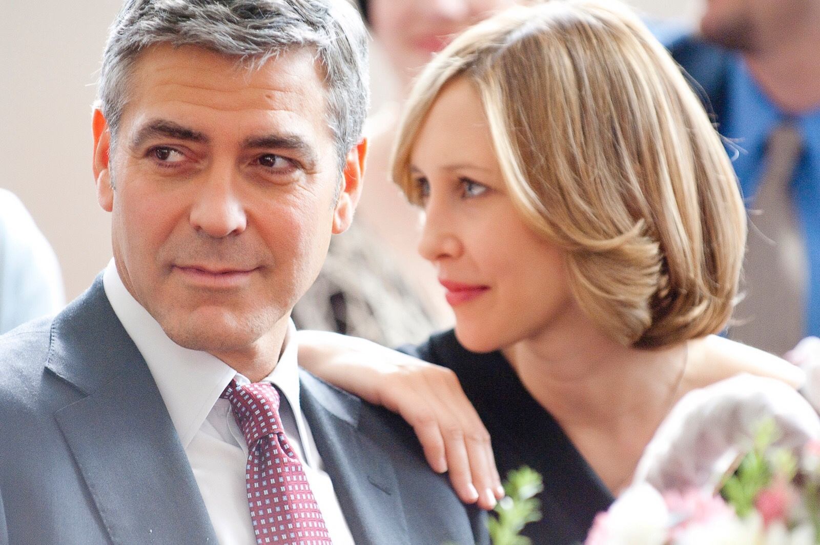 Clooney and Farmiga; she has her hand on his shoulder as both look towards the left