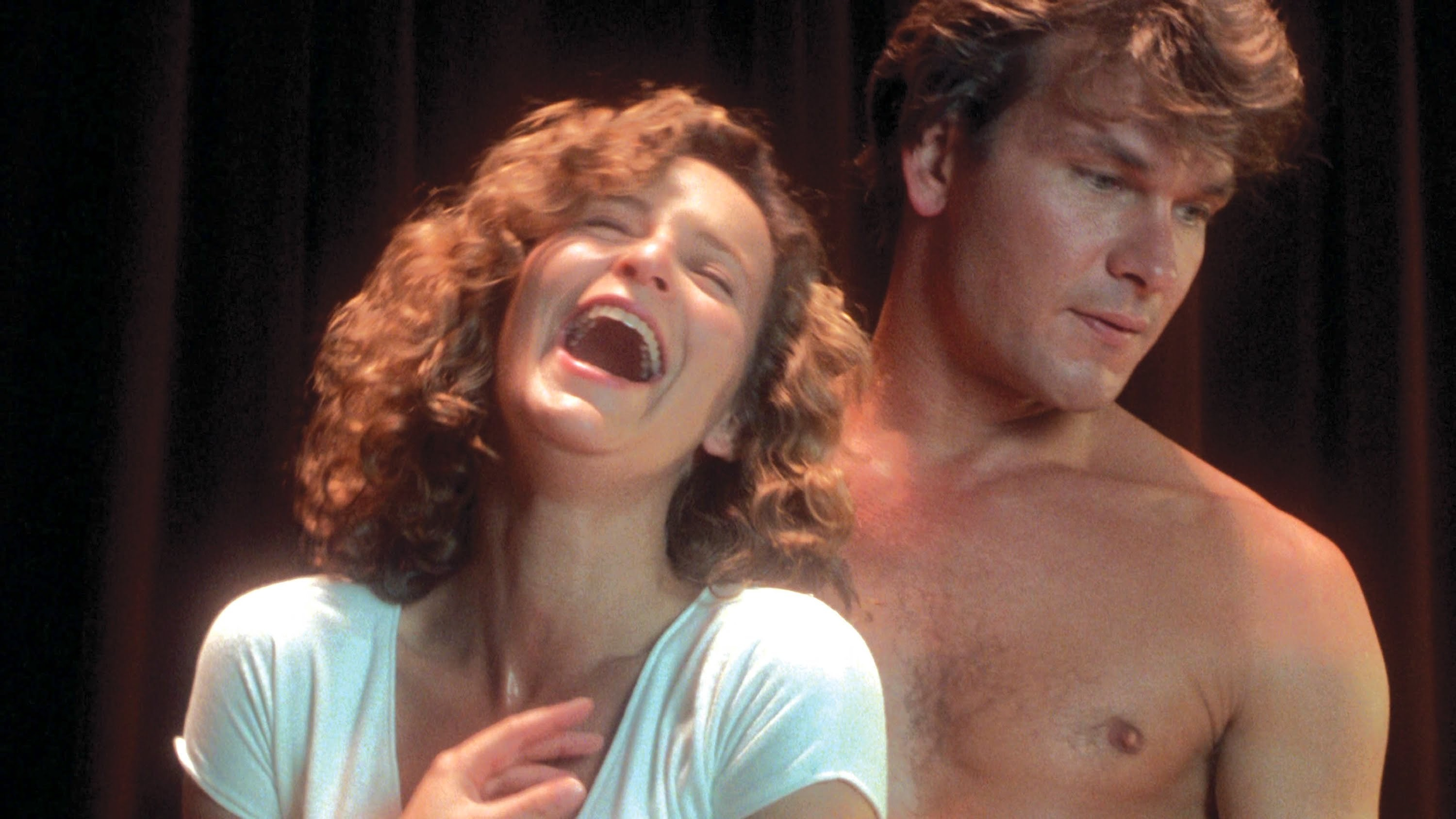 Swayze, topless, standing behind a Grey who is laughing hysterically