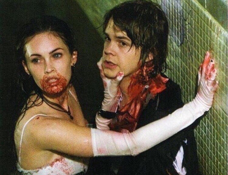 Jennifer and Chip, dressed for the prom and in a dirty pool. Jennifer has blood all around her mouth after taking a bite from Chip's neck