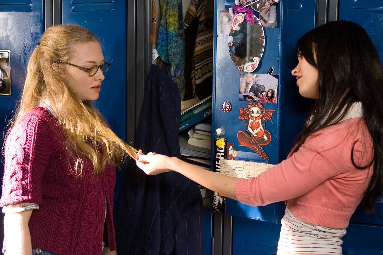 Jennifer and Needy in front of their school lockers. Jennifer is pulling a strand of Needy's hair