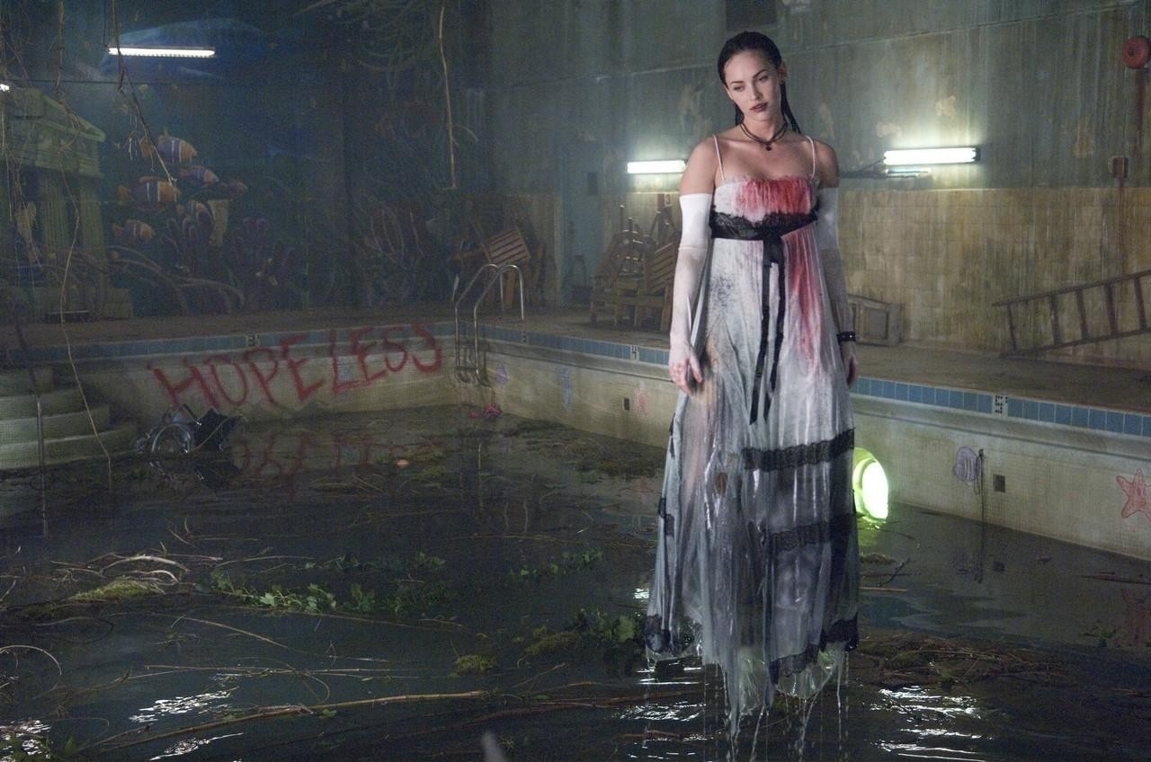 Jennifer in a prom dress, covered in blood, floating above a dirty pool