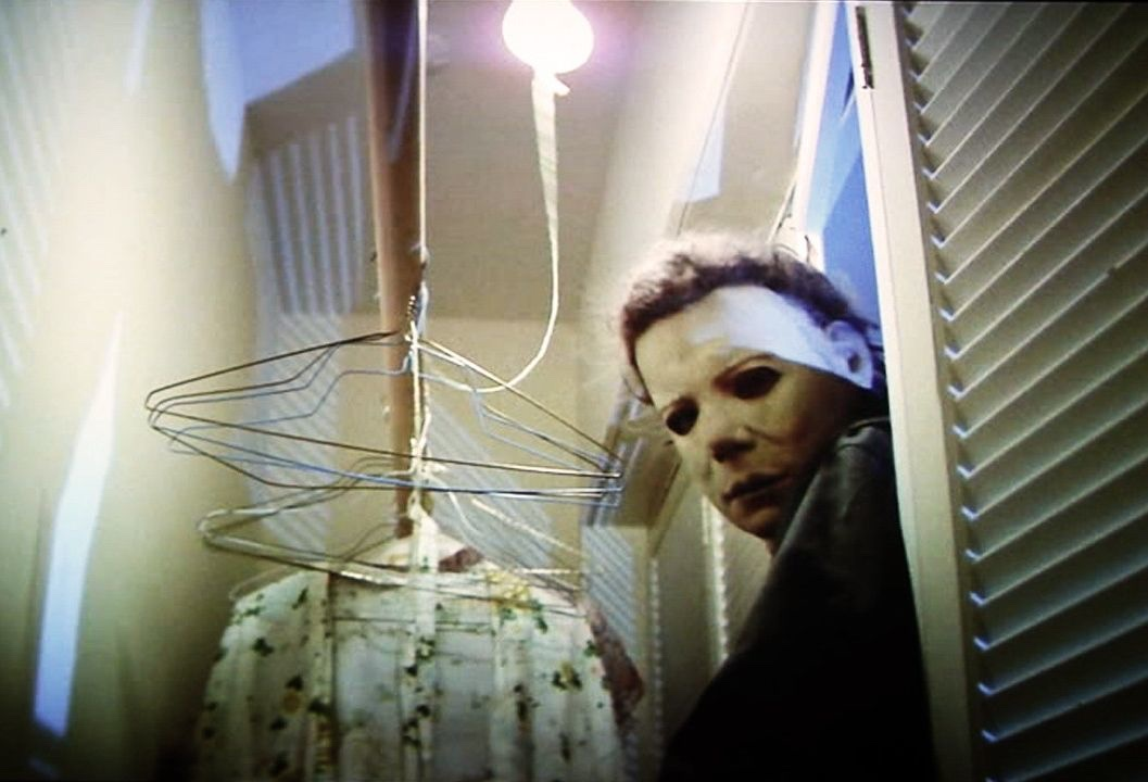 Image from Halloween showing masked Michael Myers bursting into a wardrobe