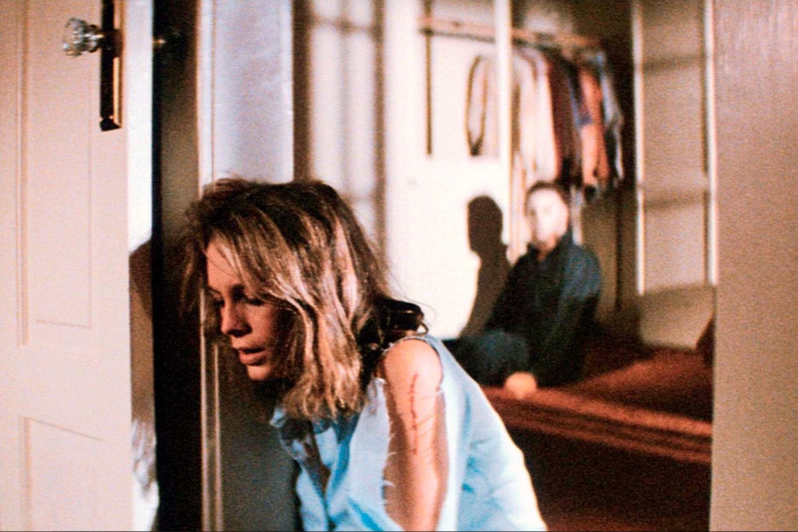 Image from Halloween showing Laurie sat by a door with Mike Myers sitting up in the background