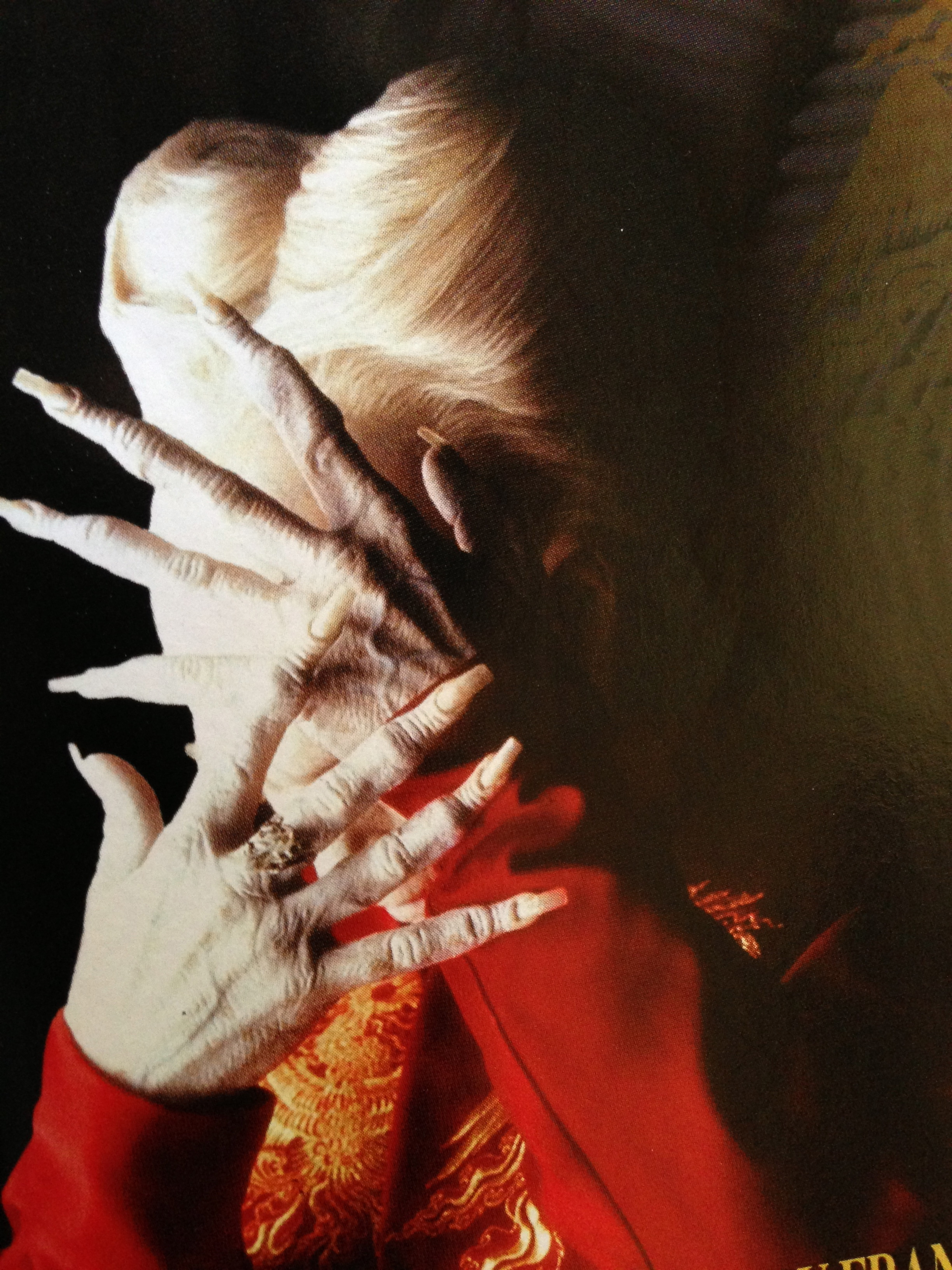 Image from Dracula showing Oldman in full elderly vampire make up, bouffant white hair and long fingers with his hands dramatically over his face