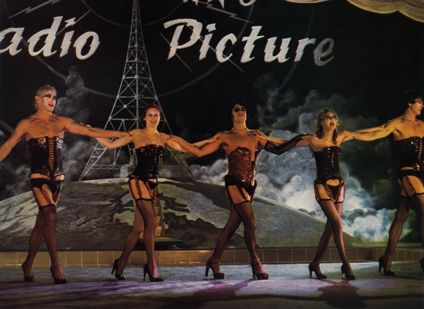 Image from Rocky Horror, showing the main characters dancing a chorus line in stockings and suspenders