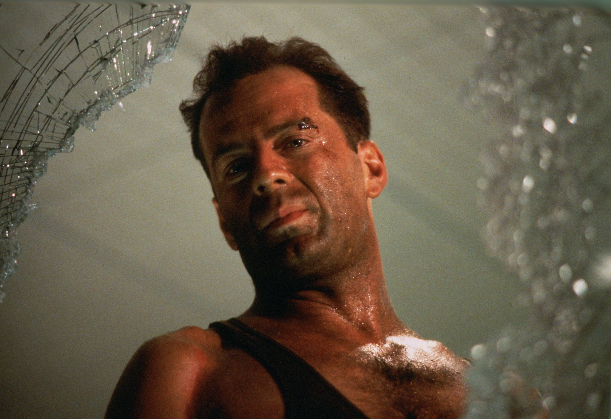 An image from Die Hard showing McClane looking out of a broken window