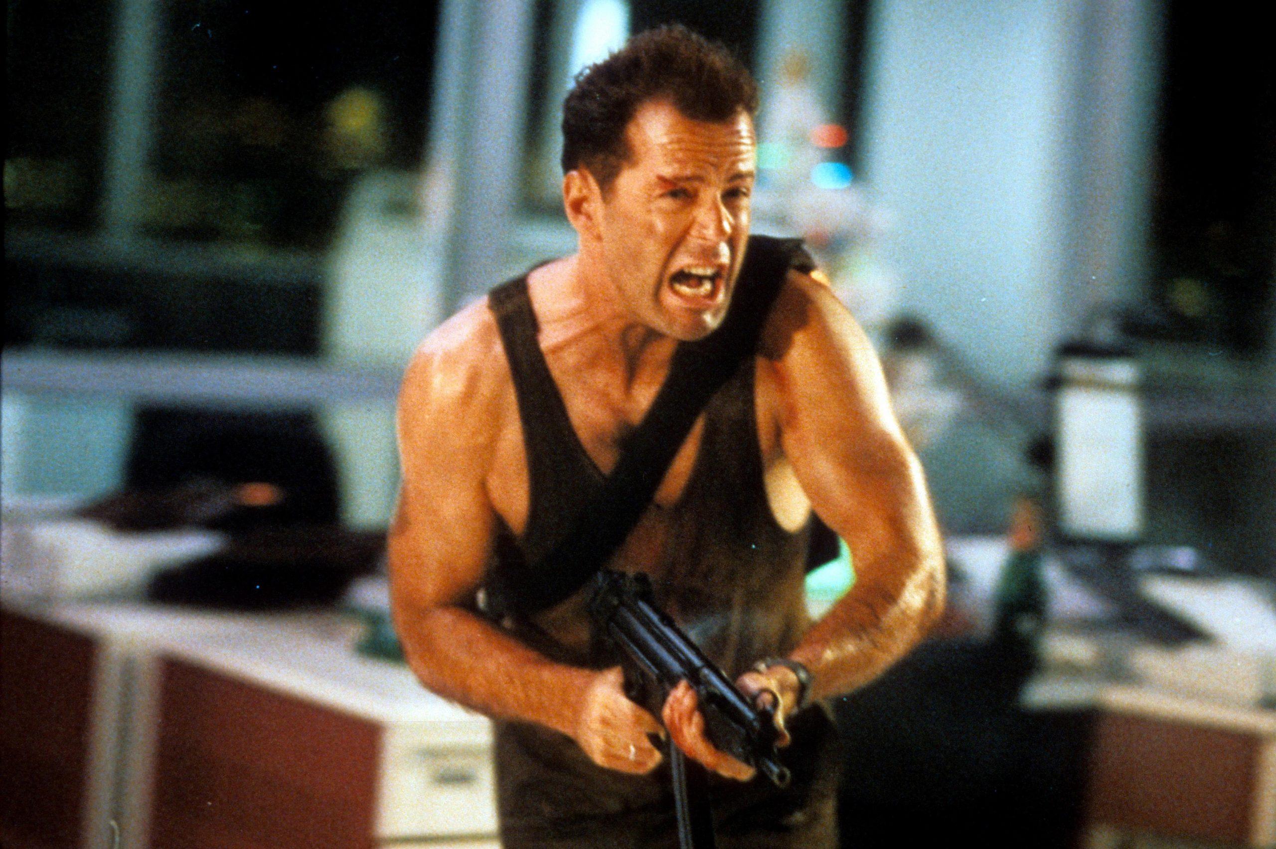 McClane running forward screaming and brandishing a gun