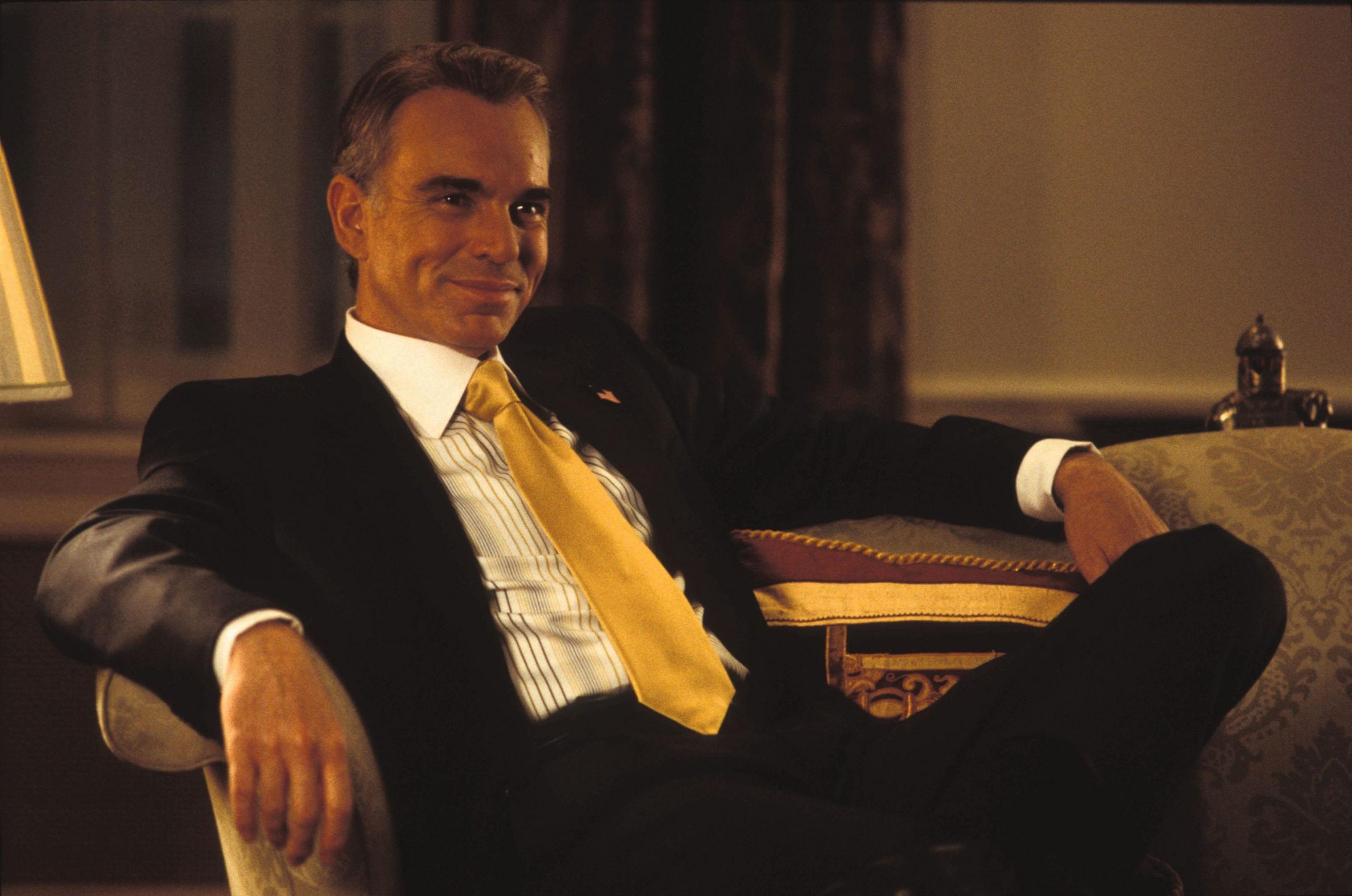 An image from Love Actually showing Billy Bob Thornton as the president looking very smug
