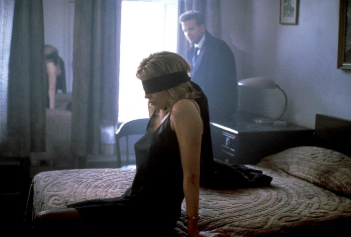 An image from Nine 1/2 Weeks showing Elizabeth blindfolded and John watching