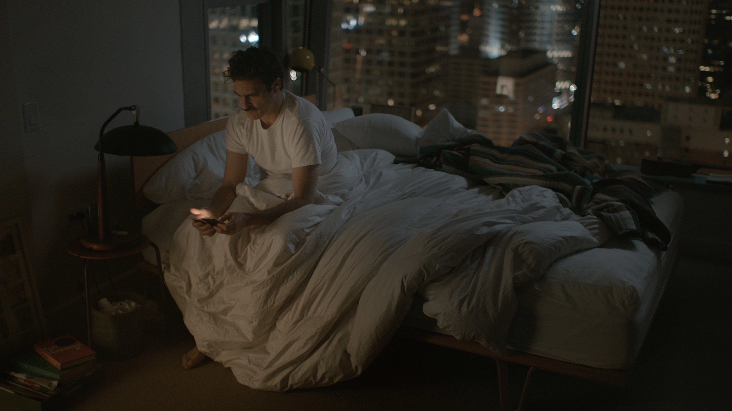 An image from Her showing Theodore in bed looking at his phone