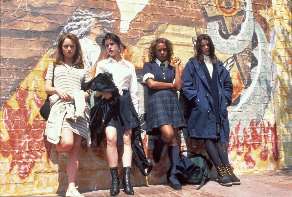 The four girls from The Craft leaning against a wall